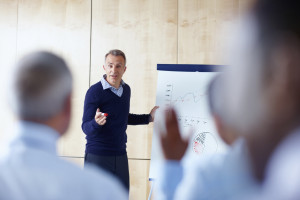 Senior Business man giving presentation to group of colleagues